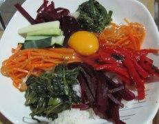 Bibimbap, verduras preparadas con sabores distintos, servidos con arroz, huevo y una pasta dulce picante de ají coreano. Bibimbap, vegetables prepared with distinct flavours, served on rice with an egg and sweet spicy Korean chili paste.